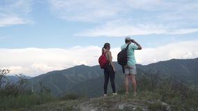 Young man traveler showing through binoculars the purpose of traveling to his girlfriend. Tourists with backpacks on top. Young travelers on the edge of the stock footage