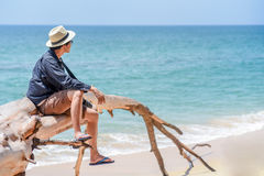 Young man traveler sitting on dead tree at the beach. Young man traveler with jean shirt and hat sitting on white dead tree near sandy beach of tropical island Royalty Free Stock Images