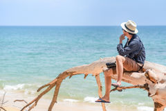 Young man traveler sitting on dead tree at the beach. Young man traveler with jean shirt and hat sitting on white dead tree near sandy beach of tropical island Royalty Free Stock Image