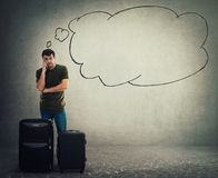 Young man traveler standing behind his luggage and waiting stock image