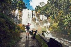 Traveler near waterfall. Young man traveler standing near Wachirathan waterfall in tropical rainforest. Chiang Mai Province, Thailand Royalty Free Stock Photo