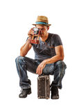 Young man traveler takes a shot while sitting on suitcase over w Stock Images
