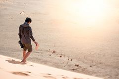 Young man traveler walking down the sand dune with bear foot. Young Asian man traveler and photographer walking down the sand dune with bear foot carrying his Royalty Free Stock Photo