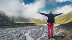 Young man traveler walking and enjoys view of summer spring mountains, rear view with copy-space. Concept of achieving motivation stock image