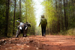 A young man traveling alone on forest with luggage and motorcycl Royalty Free Stock Images