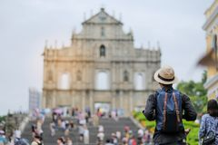 Young man traveling backpacker with hat, Asian hipster traveler looking to Ruins of St. Paul`s, Historic Centre of Macau, a UNESC stock image