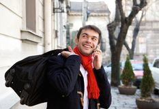 Young man traveling with bag calling by mobile phone. Portrait of a young man traveling with bag calling by mobile phone Stock Image