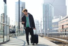 Young man traveling with bag and mobile phone Stock Image