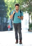 Young man traveling with bag and mobile phone. Full length portrait of a young man traveling with bag and mobile phone Stock Photos