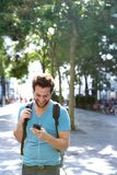 Young man traveling with bag and mobile phone. Portrait of a young man traveling with backpack and mobile phone Stock Photo