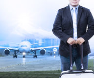 Young man and traveling luggage staning in front of air plane ta Royalty Free Stock Image