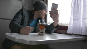 A young man is traveling on a train. A young man drinks tea from a special glass cup in a train, looks into his white smartphone and takes a video call, talks stock footage