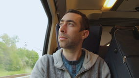 Young man traveling on a train and looks out the window. A blue suitcase is next to him stock video footage