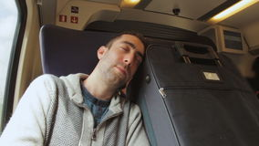Young man traveling on a train and sleep on blue suitcase next t stock footage