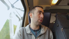 Young man traveling on a train and talking with someone. A blue suitcase is next to him stock video