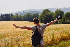 Young man traveller spreads his arms and looks at the golden wheat field, blue sky and hills covered with the green forest royalty free stock photography