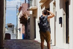Traveller with camera and backpack takes pictures of the foreign city during the vacation, Crete, Greece stock images