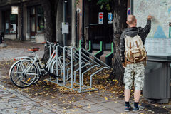 Young man traveller looking to city map on street. Young beard man traveller looking to city map on street Royalty Free Stock Photo