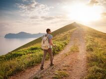 Young man travels alone on the backdrop of the mountains. Young man travels alone walking on trail and enjoying on view of mountains and sea landscape at sunset