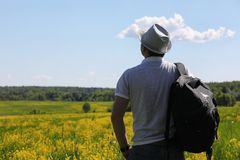Young man travels with a backpack. On a summer day outdoorsr Stock Photo