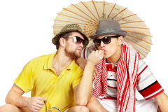 Young man treats another banana. Two men sitting in a summer dress Royalty Free Stock Photos