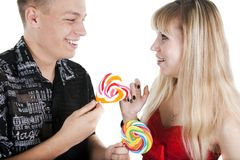 Young man treats the girl with a lollipop Royalty Free Stock Photo