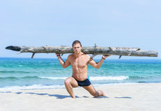 Young man with a tree trunk on his shoulders. Sporty, healthy and muscled man training on a summer beach Royalty Free Stock Images