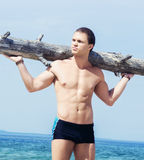 Young man with a tree trunk on his shoulders. Sporty, healthy and muscled man training on a summer beach Royalty Free Stock Photography
