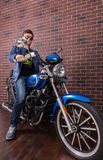 Young Man in Trendy Fashion on his Motorbike. Attractive Young Man Wearing Trendy Fashion on his Blue Motorbike Beside the Brick Wall, Looking at the Camera Royalty Free Stock Photography