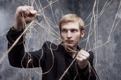 Young man tries to break the shackles. Concept of manipulation and slavery Stock Photos