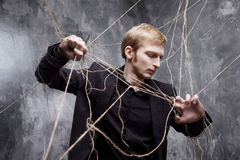 Young man tries to break the shackles. Concept of manipulation and slavery Stock Photography