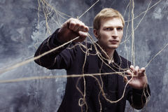 Young man tries to break the shackles. Concept of manipulation and slavery Stock Photo