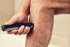 Young man trimming his legs with an electric trimmer Royalty Free Stock Image