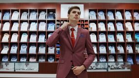Young man try on classical suit in the suit shop. 4K stock footage