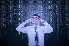 Young man try to solve binary code Stock Photo