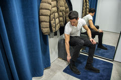 Young Man Trying on Clothes in Clothing Store. Young Handsome Man Trying on Clothes in Clothing Store's Changing Room in Front of a Mirror or in Room Closet royalty free stock images