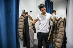 Young Man Trying on Clothes in Clothing Store Stock Photo