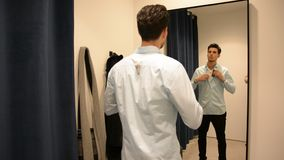Young Man Trying on Clothes in Clothing Store. Rear View of a Young Handsome Man Trying on Clothes in Clothing Store's Changing Room in Front of a Mirror or in stock video