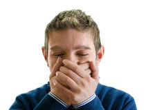 Young man trying not to laugh. Young man covering his mouth with hands, trying not to laugh Royalty Free Stock Photo