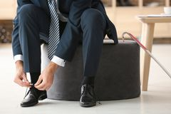 Young man trying on shoes. In shop Royalty Free Stock Image
