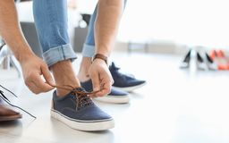 Young man trying on shoes. In store Stock Images