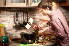 Young man trying to catch toasts popping out of toaster Stock Photography