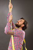 Young man trying to climb a rope-business concept- Stock Images