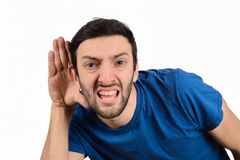 Young man trying to listen something stock photo