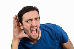 Young man trying to listen something royalty free stock photography