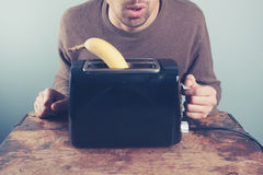 Young man trying to toast a banana Royalty Free Stock Photos