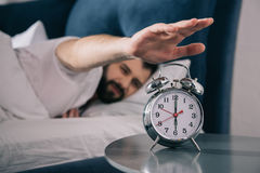 Young man trying to turn off alarm clock while lying in bed at morning. Bearded young man trying to turn off alarm clock while lying in bed at morning Stock Photography