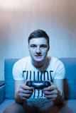Young man trying to win the video game at  home Royalty Free Stock Images