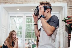 Young man trying virtual reality glasses while people looking at him and laughing in restaurant stock photo