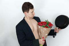 Young man with tulip bouquet and frying pan Stock Image